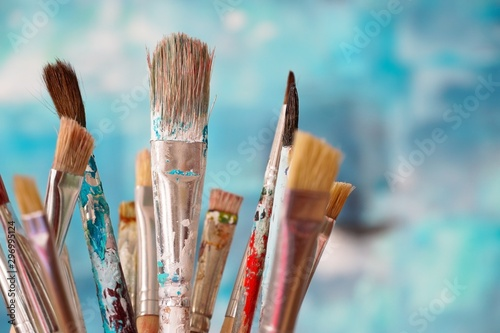 Paint brushes in front of blurred canvas Canvas-taulu