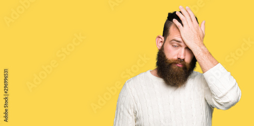 Fotografía  Young hipster man wearing winter sweater surprised with hand on head for mistake, remember error