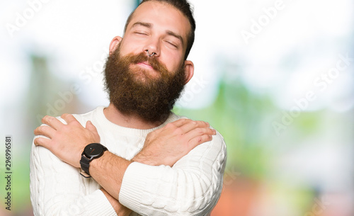 Cuadros en Lienzo Young hipster man wearing winter sweater Hugging oneself happy and positive, smiling confident