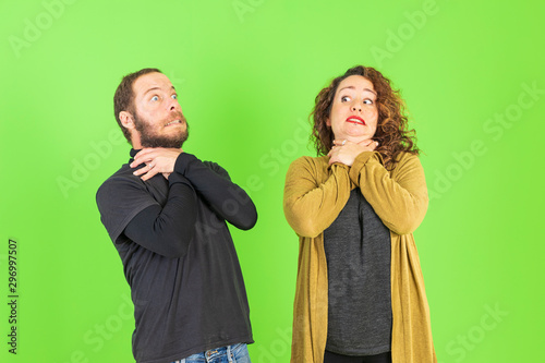 Young beautiful couple together over green background shouting and suffocate by painful strangle Tablou Canvas