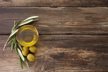 olive oil and olive branch backlit on old wooden background