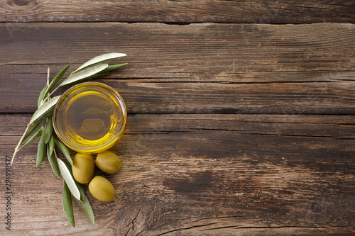 Photo olive oil and olive branch backlit on old wooden background