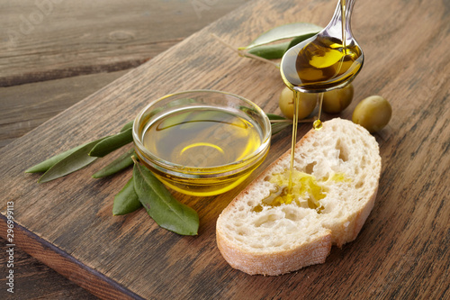 Fototapeta slice of bread seasoned with olive oil on wooden background