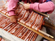 Leinwanddruck Bild - Close up man's arms wprking on traditional weaving technique Ikat for making scarfs or Macana or other fabric by hand with cotton threads, design are traditional for Gualaceo, Azuay province, Ecuador