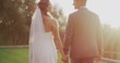 Happy diverse bride and groom holding hands and smiling at each other walking together at sunset on their wedding day