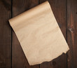 canvas print picture - roll of untwisted brown paper on a wooden surface from old boards