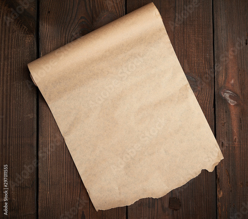 Valokuvatapetti roll of untwisted brown paper on a wooden surface from old boards