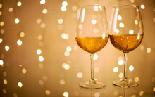 Pair Of Wine Glasses On Glass Table Against Golden Bokeh Lights Background, Festive And Fun Concept