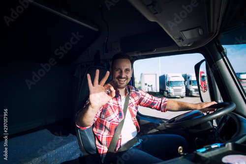 Truck driver loving his job and showing okay gesture sign while sitting in his truck cabin Fotobehang