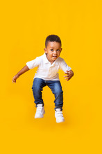 Adorable Afro Baby Boy Jumping Over Yellow Studio Background