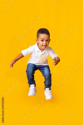 Fototapeta Adorable afro baby boy jumping over yellow studio background obraz