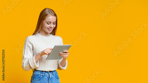 Obraz Beautiful teen girl using digital tablet over orange studio background - fototapety do salonu