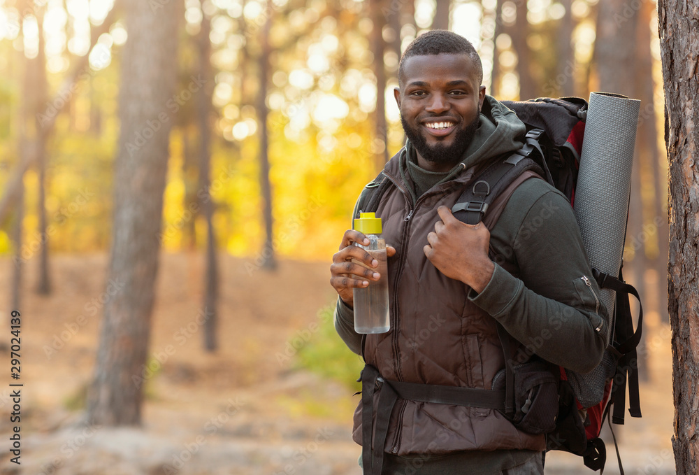 Fototapety, obrazy: African man wearing backpack standing over forest background