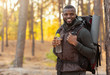 African man wearing backpack standing over forest background