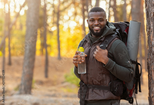 Fotografie, Obraz  African man wearing backpack standing over forest background