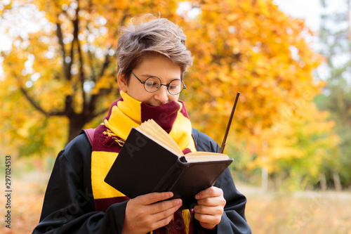 Cute Boy in Halloween costume reads book in autumn park. Cosplay