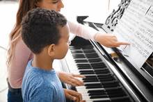 Woman Teaching Little African-American Boy To Play Piano At Home
