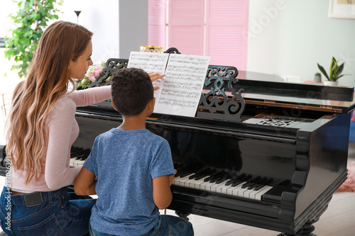 Photo Woman teaching little African-American boy to play piano at home