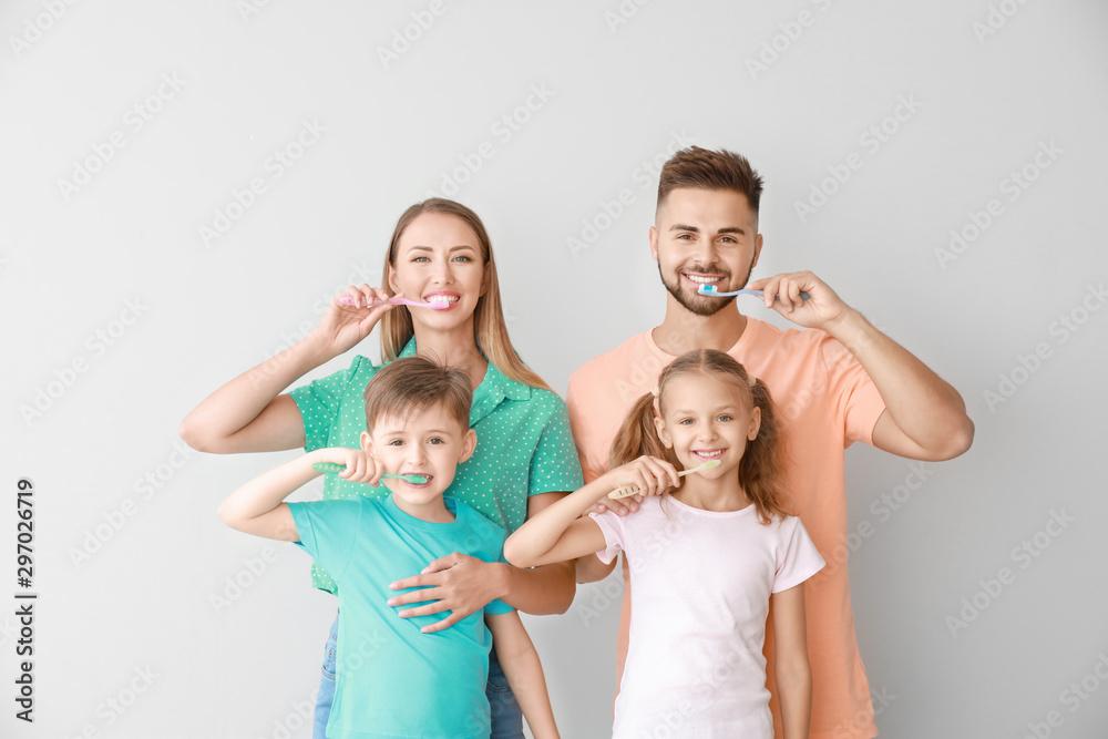 Fototapety, obrazy: Portrait of family brushing teeth on light background