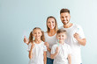 Portrait of family with toothbrushes on light background