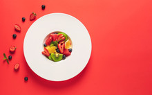 Plate With Tasty Fruit Salad On Color Background