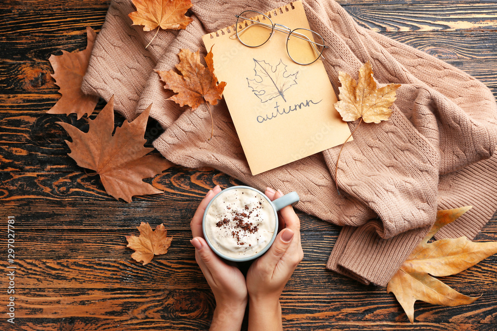 Fototapety, obrazy: Female hands with hot chocolate in cup, warm sweater and dry leaves on wooden background