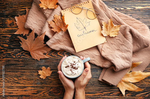 Fototapeta Female hands with hot chocolate in cup, warm sweater and dry leaves on wooden background obraz