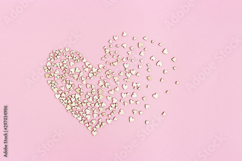 Photo sur Toile Roses Many small wooden hearts flying to the sides. Shattered feelings. Broken love. Love concept on pink paper background with copy space.