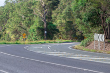 Winding Street Road Leading Through The Mountains With Thick Australian Bush And Yellow Street Signs