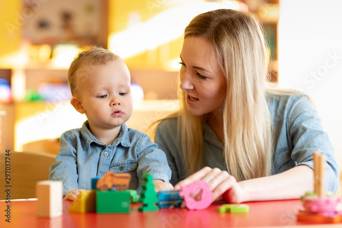 Stampa su Tela Mother and child son are talking and smiling while playing with educational toys