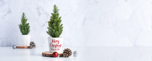 Merry Christmas Tree With Pine Cone,decor Red Xmas Ball On Wood Log At White Table And Marble Tile Wall Background.clean Minimal Simple Style.holiday Still Life With Space To Adding Text