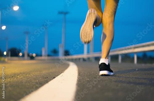 Movement. Woman legs running on asphalt road. Fototapet