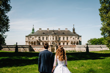 Newlyweds Are Walking Their Backs To The Vintage сastle, Renaissance Palace For The Wedding Ceremony. Photo Shoot Near Medieval Pidhirtsi Castle, Lviv Region, Ukraine.