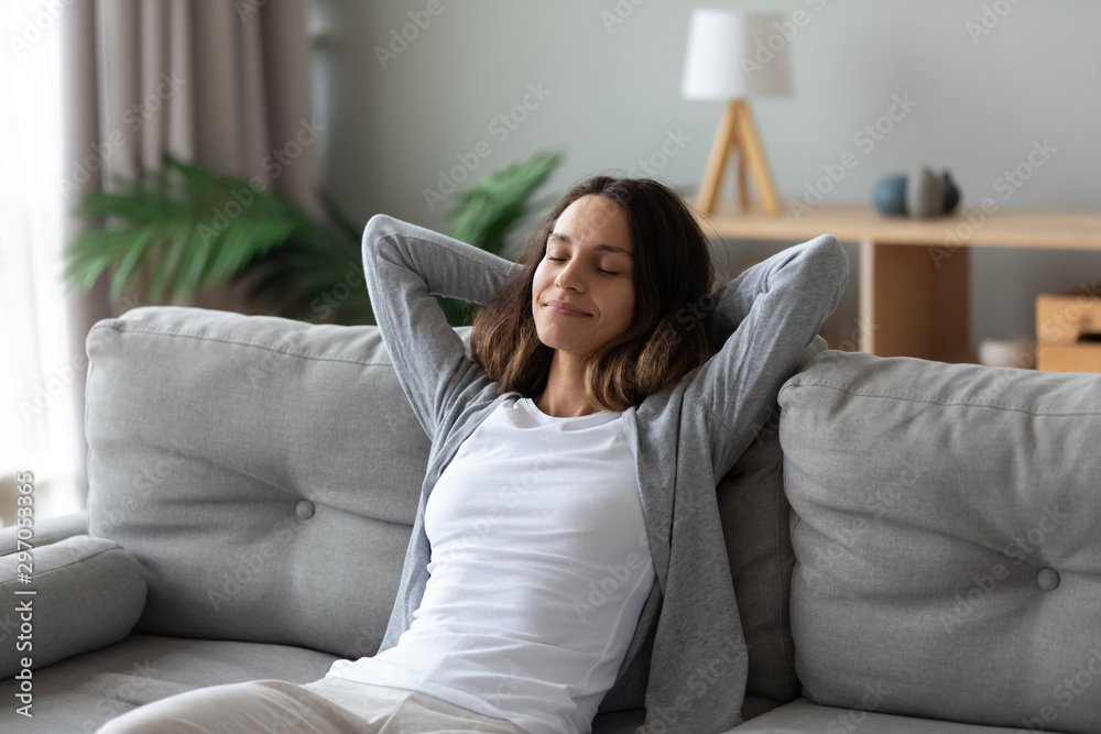 Fototapety, obrazy: Tranquil smiling biracial millennial woman leaning on sofa.