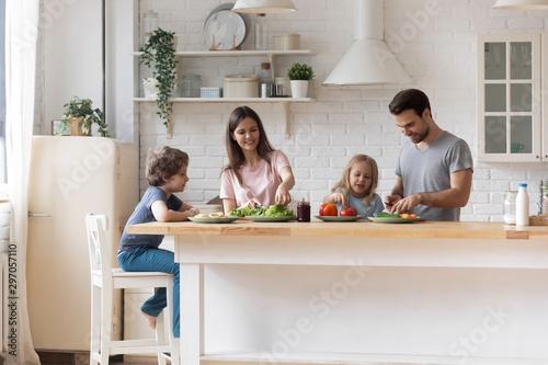 Fototapeta Happy family with little children preparing salad together obraz