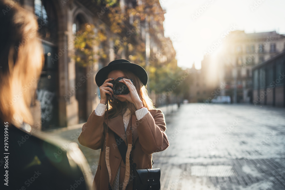 Fototapety, obrazy: Blogger photoshoot concept. Photographer with camera take photo model girlfriend. Tourist smiling girl travels in Barcelona holiday with traveler friend. Sunlight flare street in europe city