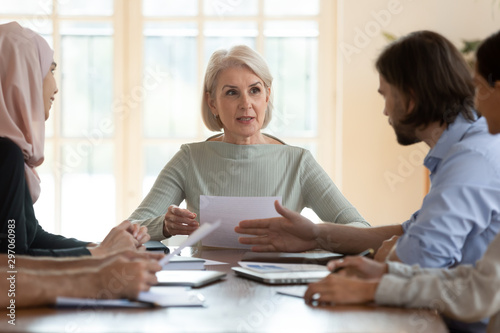 Fotomural  Mature company ceo holding document leading corporate group meeting
