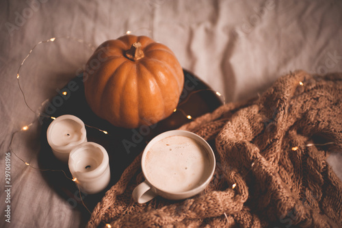 Fotomural  Cup of tasty latte, burning candles, fresh pumpkin and knitted scarf in bed closeup
