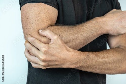 Stampa su Tela  man with black t shirt and hand on elbow, injury concept