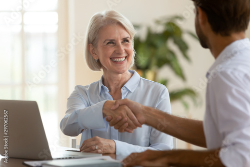 Fotografía Smiling mature saleswoman handshake businessman client customer at business meet