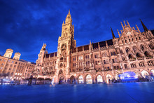 Night View Of The Main Attraction Of Munich And All Of Bavaria - Illuminated Building Of The New Town Hall At Night. Tourism And Travel To Germany Concept