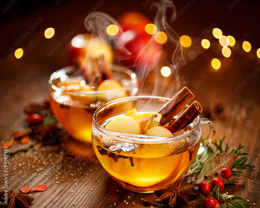 Fototapeta Mulled cider with apple slices, cinnamon, cloves, anise stars and citrus fruits in glass cups on a wooden rustic table. Delicious christmas hot drinks on a wooden rustic table.
