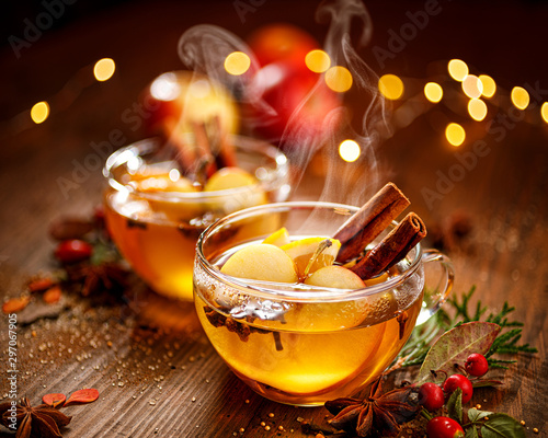 Fototapeta Mulled cider with apple slices, cinnamon, cloves, anise stars and citrus fruits in glass cups on a wooden rustic table