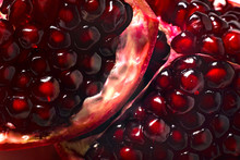 Delicious Beautiful Pomegranate On Dark Background. Close-up Image Of A Red Pomegranate