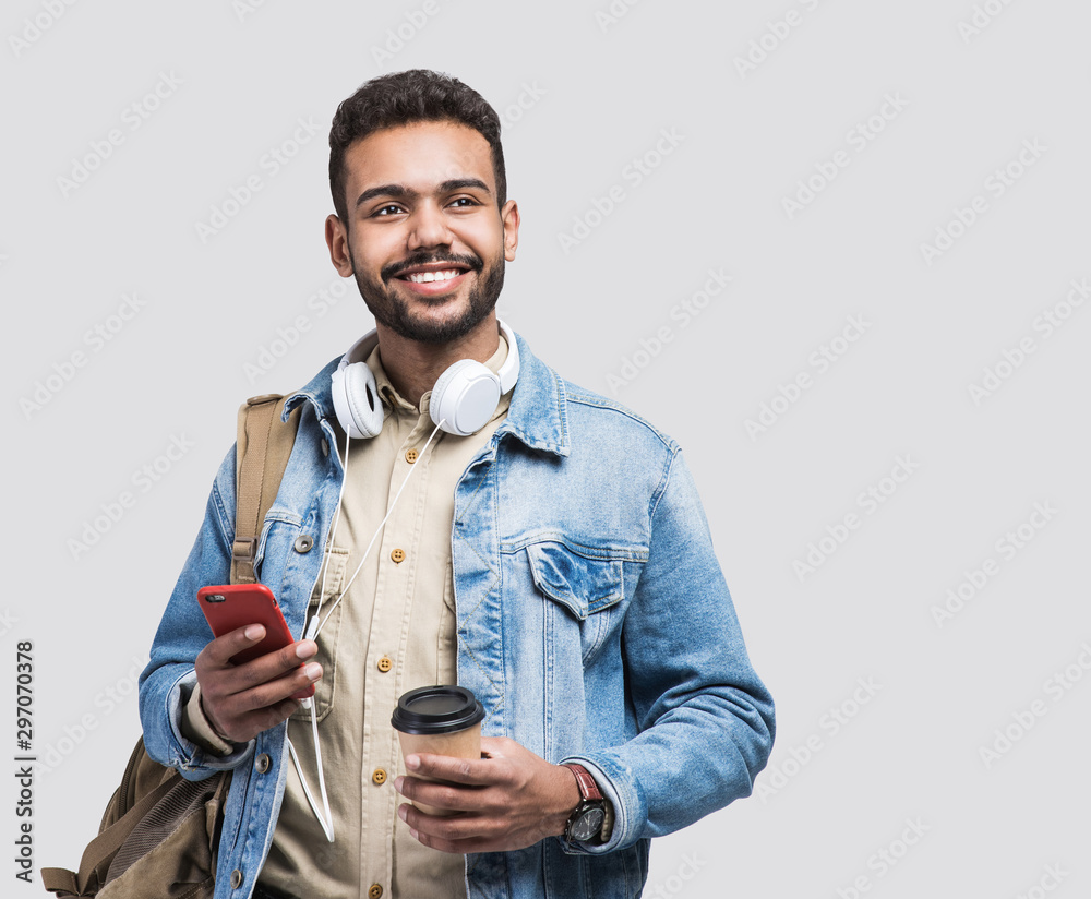 Fototapeta Young handsome man with backpack holding smart phone and coffee. Smiling student going on a travel. Isolated on gray background