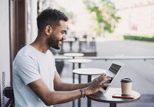 Smiling man student using digital tablet in a city Fototapeta