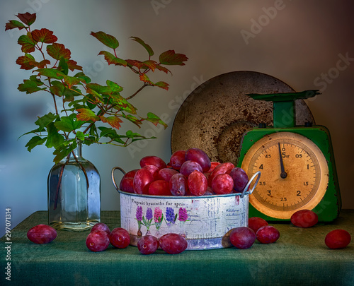 Fototapeta Still life with ripe plums, old weights and branches with beautiful leaves. Vintage. obraz
