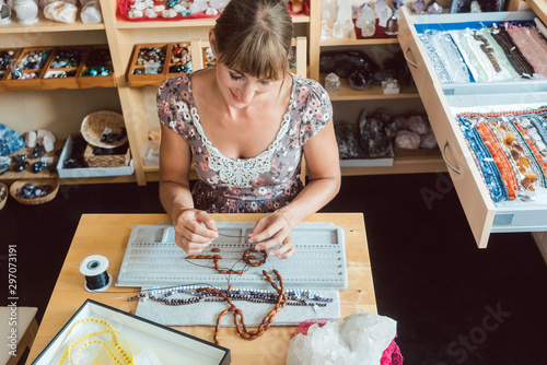 Fototapeta Woman working on a gemstone necklace as a hobby obraz