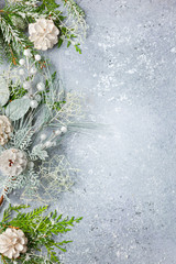 Christmas or winter background with a border of green and frosted evergreen branches and pine cones on a grey vintage board. Flat lay