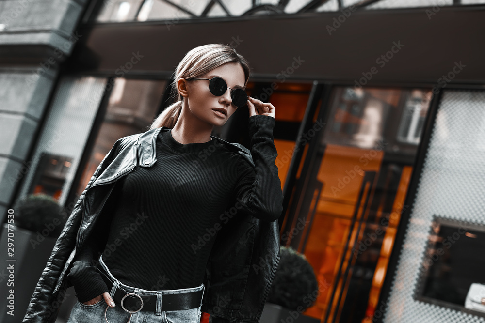 Fototapeta Fashion stylish woman in leather jacket, jeans, sweater and sunglasses walking on road on shops background. Elegant trendy outdoors portrait of pretty girl model on city street